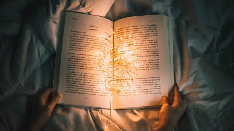 [Image Description- Person holding string lights on opened book]