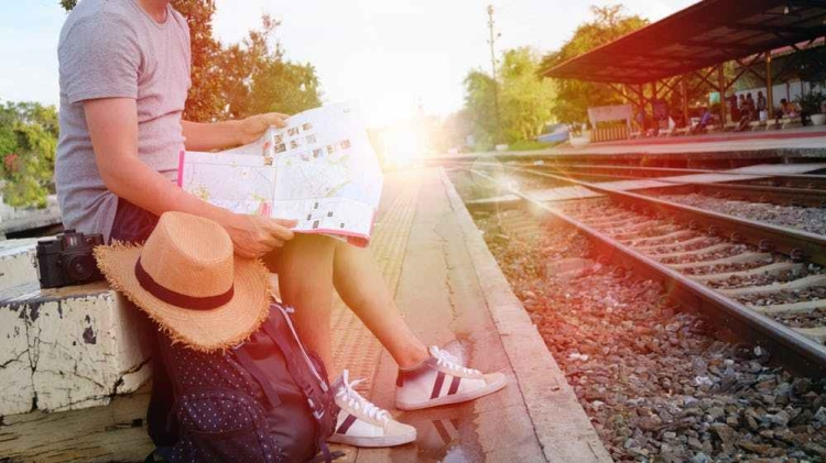 [Image Description- Person sitting on side of a railway track, holding a map with hat, camera and bag kept on the side]