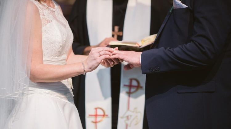 [Image Description- Bride putting ring on grooms finger]